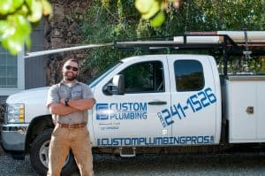 John Jones of Custom Plumbing stands near his work truck. Train. Build. Succeed.